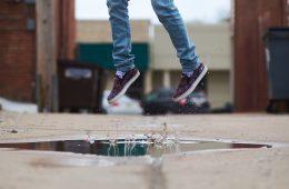chico saltando sobre charco